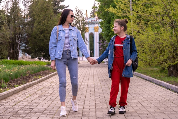 어머니와 공원에서 산책, 손을 잡고, 긴 머리와 도시에서 놀고 십 대 소녀, 라이프 스타일 가족과 함께 행복 한 젊은 백인 여자