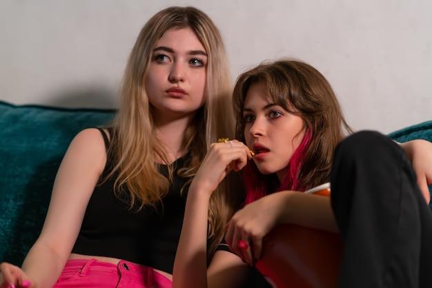 Мать и дочь-подросток вместе смотрят телевизор