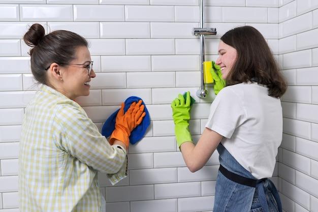母とティーンエイジャーの娘がバスルームで一緒に掃除しています。家で母親を掃除するのを手伝っている女の子。十代の若者たちと両親、人間関係、清潔さと家事、家事