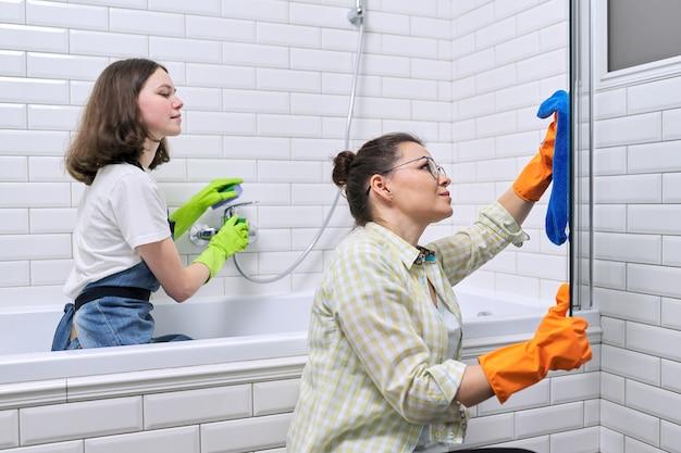 엄마와 십대 딸이 욕실에서 함께 청소합니다. 집에서 청소하는 어머니를 돕는 소녀. 십대와 부모, 관계, 청결과 가사, 가사
