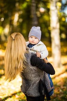 金の秋の公園を歩く母と子供