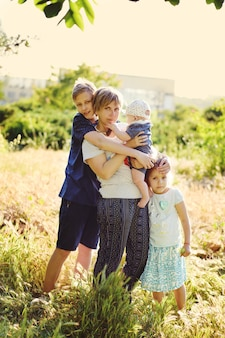 엄마와 세 아이가 야외에 서 있다