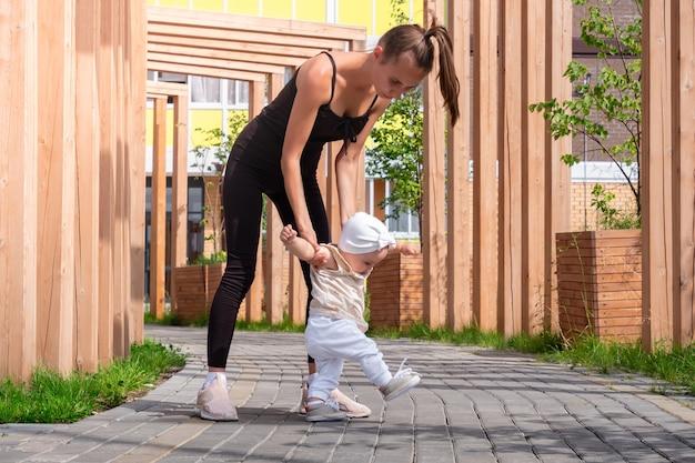 母と幼児の娘が街の中庭を歩く子供は歩くことを学ぶ