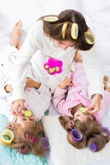 母と2人の娘がベッドに横たわっている髪のカーラーで目にきゅうりを置いています