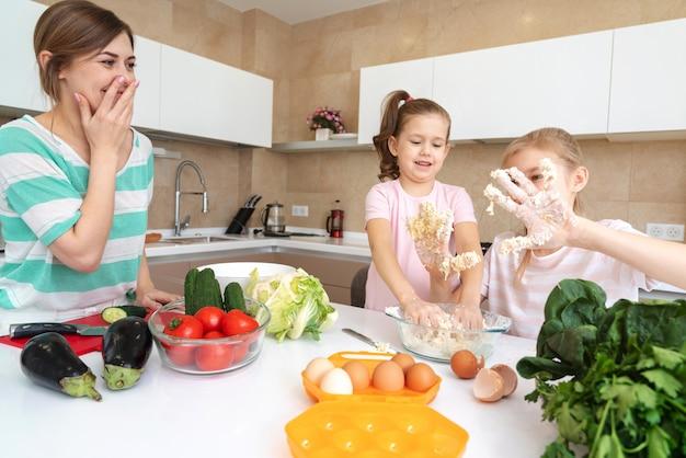 Мать и две дочери готовить на кухне и веселиться, счастливая семья и концепция одинокой матери