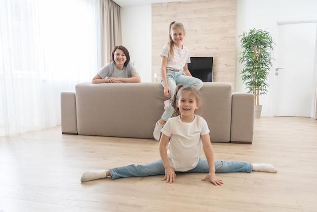 Мать и две дочери веселятся в гостиной дома. счастливая семья и концепция матери-одиночки