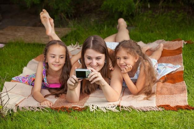 Мать и две дочери делают фото в парке