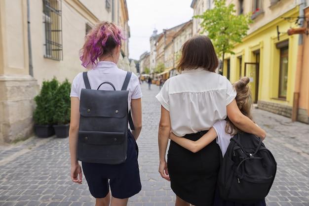 Мать и две дочери, школьник идет в школу, вид сзади