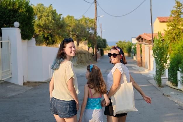 手をつないで一緒に歩いている10代と末っ子の母と2人の娘。フレンドリーな家族、幸せな親と子、夏のリゾート風景の背景、背面図