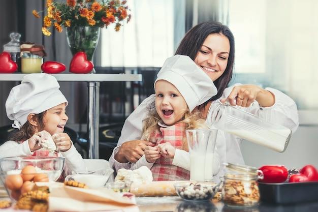 어머니와 두 행복 한 작은 아기 소녀 우유를 마시고 부엌 테이블에서 요리는 사랑스럽고 아름답습니다