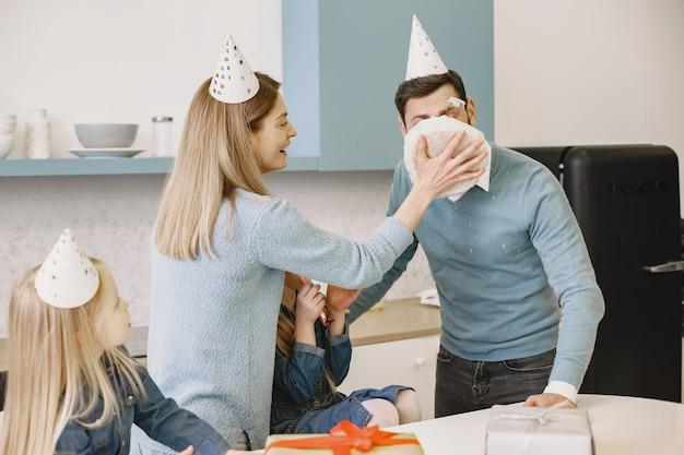 母と 2 人の娘が台所で父の誕生日を祝う 母は男の顔でケーキを叩く