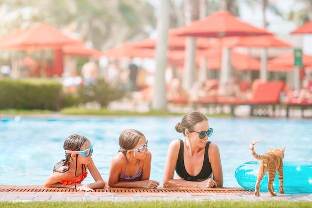 母と2人の子供が豪華なスイミングプールで夏休みを楽しんで