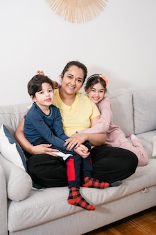 어머니와 두 아이 소파에 재미. 혼혈인. 실제 생활, 공생, 다양성, 가정에서의 편안함