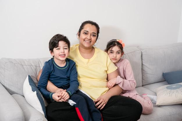 어머니와 두 아이가 웃 고 카메라를보고 소파에 앉아. 혼혈인. 실생활, 공생, 다양성