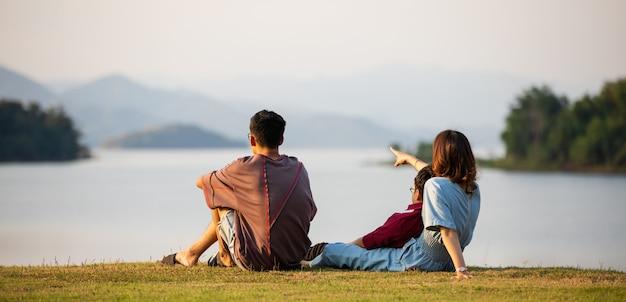 어머니와 두 아들이 큰 호수 옆에 서서 백그라운드에서 마운틴 뷰를보고 엄마가 손가락을 숲으로 가리 킵니다. 가족 여행에 대한 아이디어는 야외 여행에 함께 여행합니다.