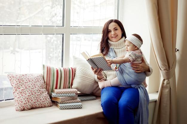 母と包まれた女の赤ちゃんは窓枠に座って、居心地の良い冬、幸せな家族のレジャーで本を読みます