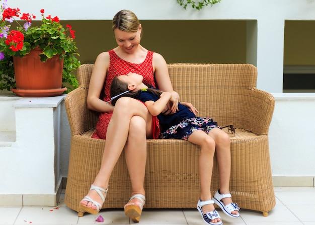 Мать и маленькая дочь сидят в кресле из ротанга в средиземноморском отеле