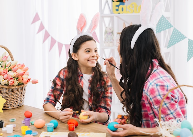 Mother applying color to her daughter's nose while decorating the easter eggs
