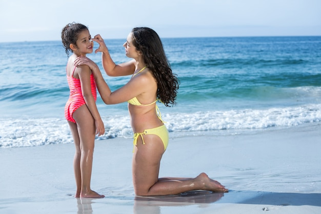 Mother applying cream to daughter