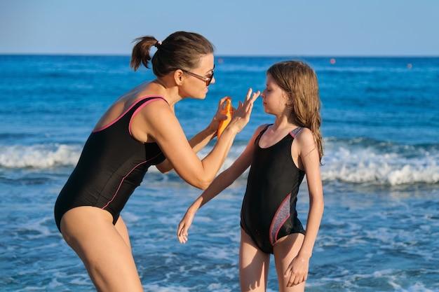 어머니는 해변에서 딸에게 자외선 차단제를 바르고, 부모와 자식이 해변 휴양지에서 쉬고, 햇볕으로부터 피부를 보호합니다.