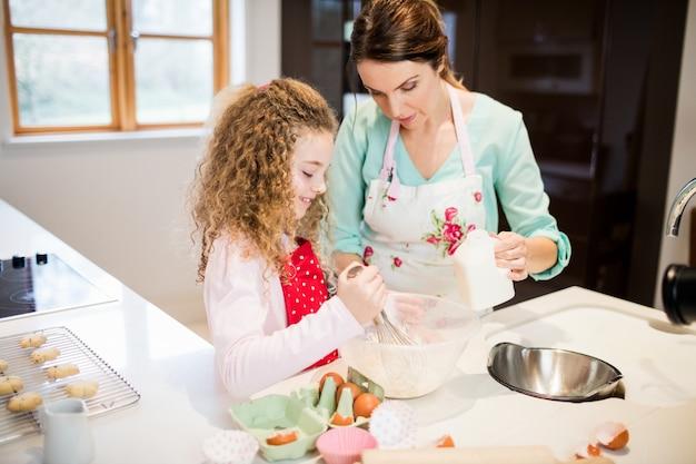 母は小麦粉を泡立てるに娘を支援します