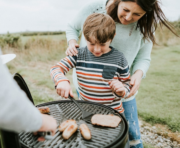 Mother assisting her child while grilling