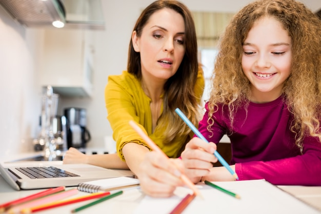 Mother assisting her daughter in drawing