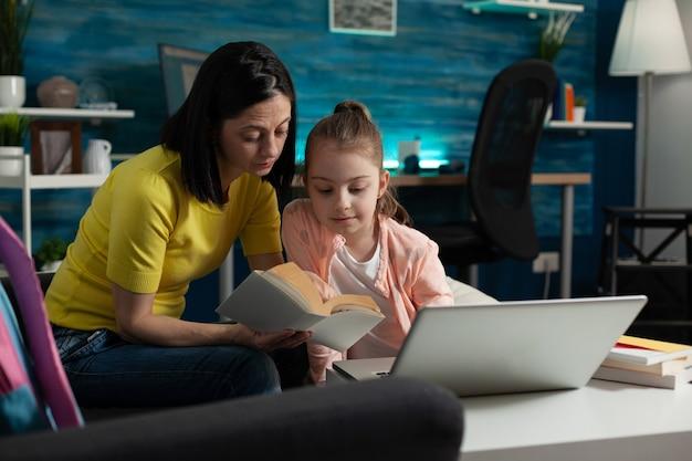 집에 앉아 있는 동안 학교 책을 읽는 어린 아이를 돕는 어머니. 온라인 강의실 강의 교육을 위해 읽고 공부하는 법을 배우는 책상 위에 현대적인 노트북을 들고 있는 똑똑한 소녀