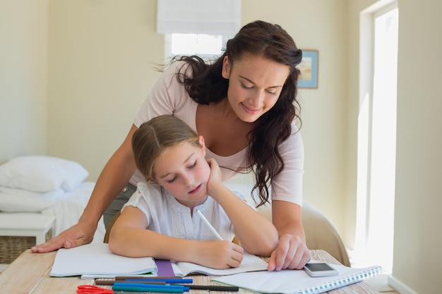 小さな娘を宿題で助ける母