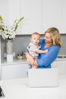 Mother and baby boy using laptop in kitchen