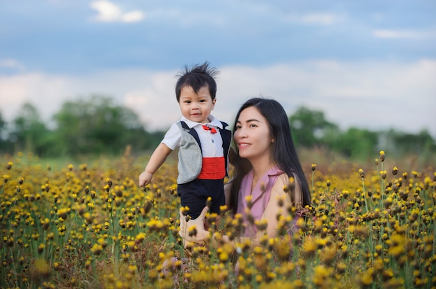 Mother and baby boy in yellow grass field in summer day.