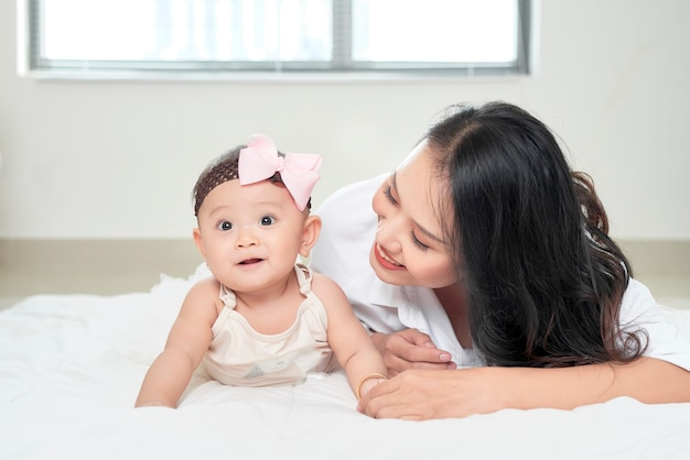Mother and baby daughter happy and beautiful home together playing on the floor on window background