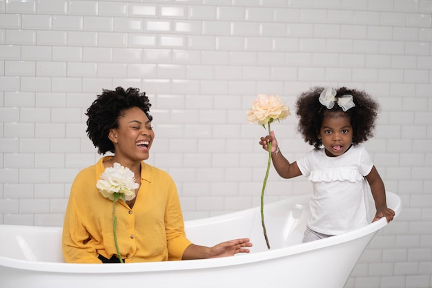 Mother and baby daughter playing together in the bathtub