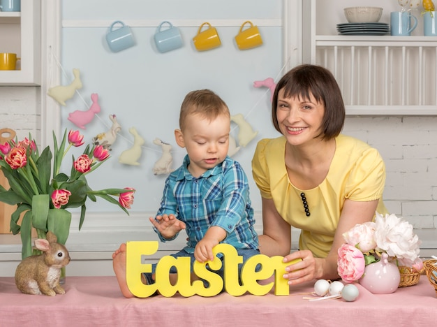 Mother and baby in the easter decorated pastel kitchen.