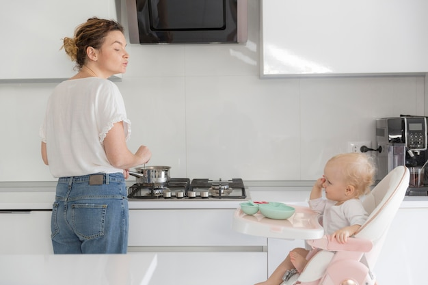 Mother and baby girl together in the kitchen