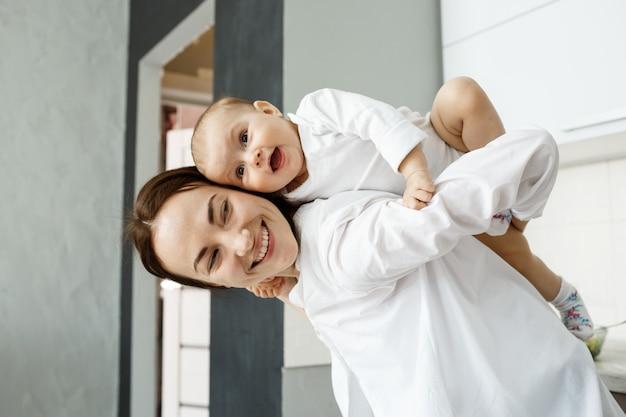 Madre e bambino si divertono, mamma carina porta il bambino sulla schiena