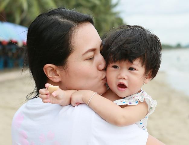 Mother and baby kissing and hugging. happy family on the beach