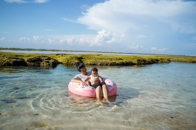 Mother and baby ride the rubber ring float when the baby in the lap