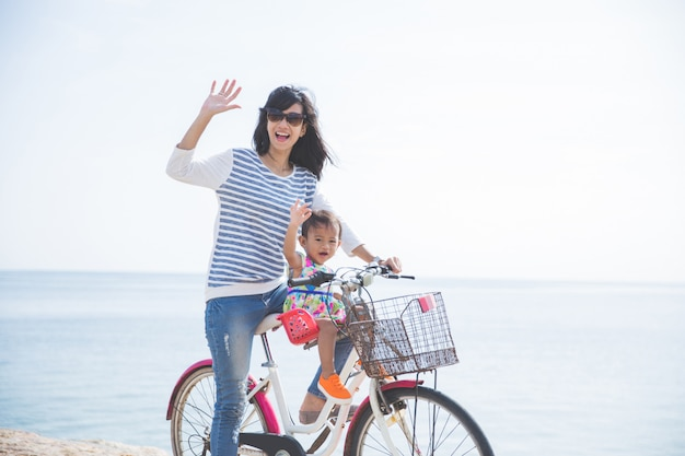 Mother and baby riding on a bicycle in the beach
