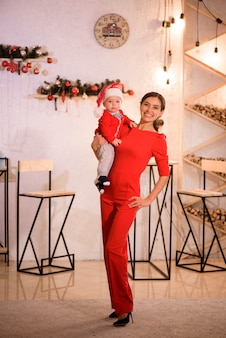 Mother and baby in santa hat play game at home near the fireplace