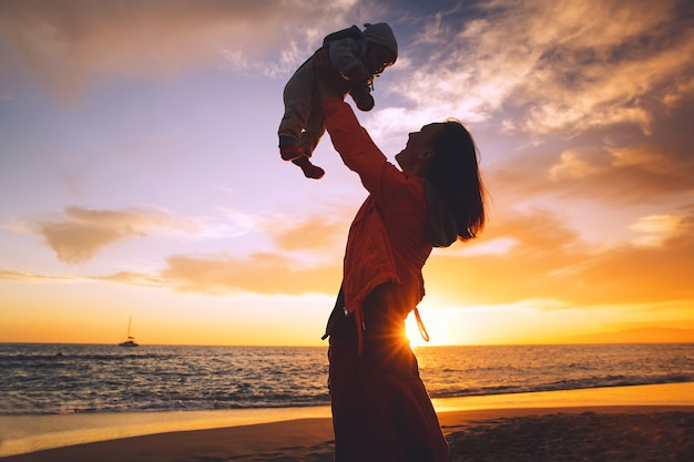 Mother and baby silhouettes at sunset on the beach ocean in summer happy family background