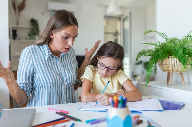 Mother becoming frustrated with daughter whilst doing homework. mom makes the best teacher ever. mother scolds a child for poor schooling and homework at home