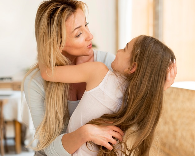 Mother being playful with daughter at home