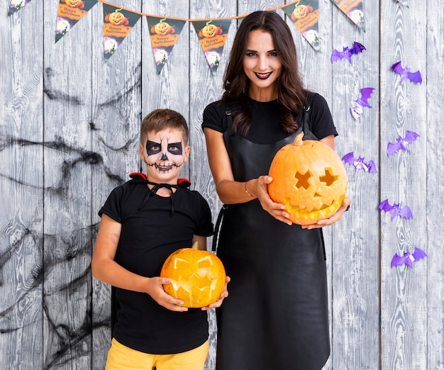 Mother and boy holding carved pumpkins