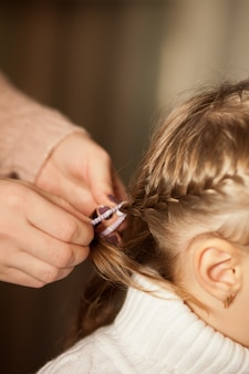 Mother braided pigtails her brunette little daughter.