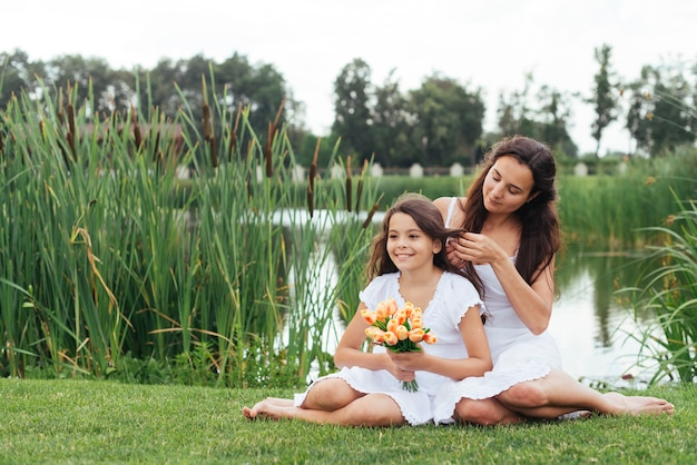 Mother braiding daughter's hair by the lake