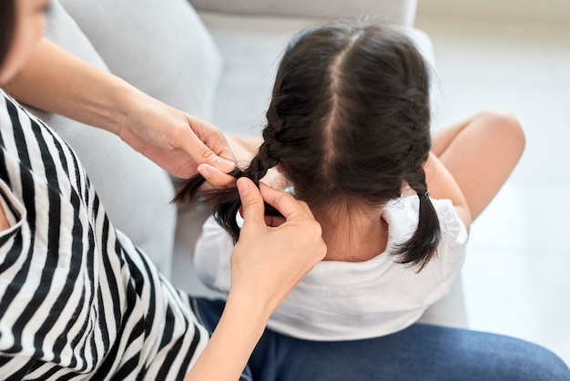 Mother braiding hair of her daughter