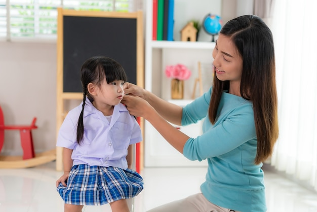 母は彼女の娘の髪を編んで椅子に座って、髪型の子供女の子を助ける単一お母さん妹を笑顔