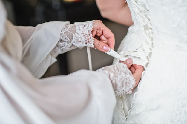 Mother of the bride helps tie the wedding dress