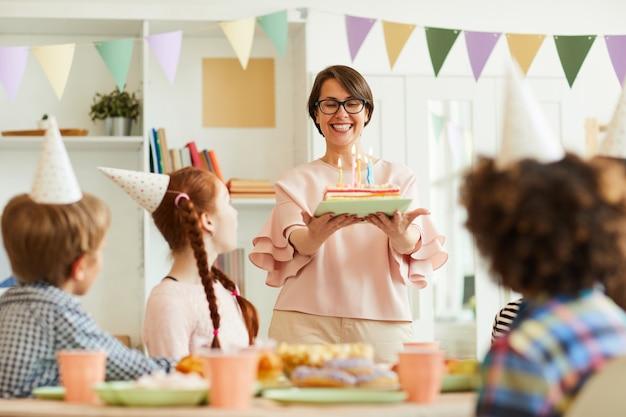Мать приносит торт ко дню рождения